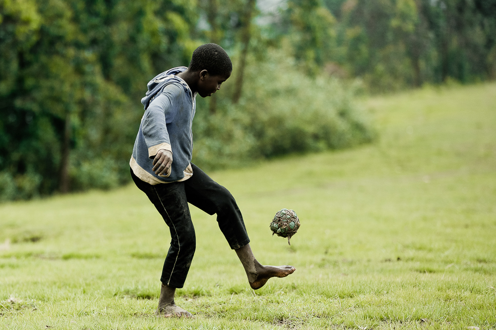 kid playing with soccer ball uganda