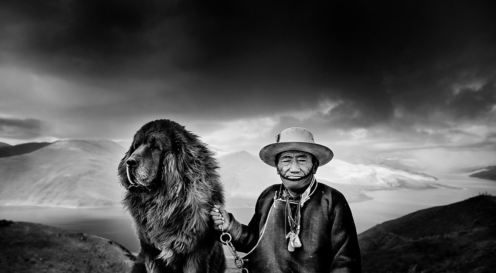 portrait of a man in Tibet with Tibetan Mastiff